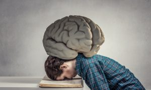 Student girl pressed with brain to opened book pages